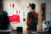 Female fashion designer contemplating drawings in studio — Stok fotoğraf