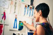 Kobieta projektant mody, kontemplując rysunki w studio — Zdjęcie stockowe