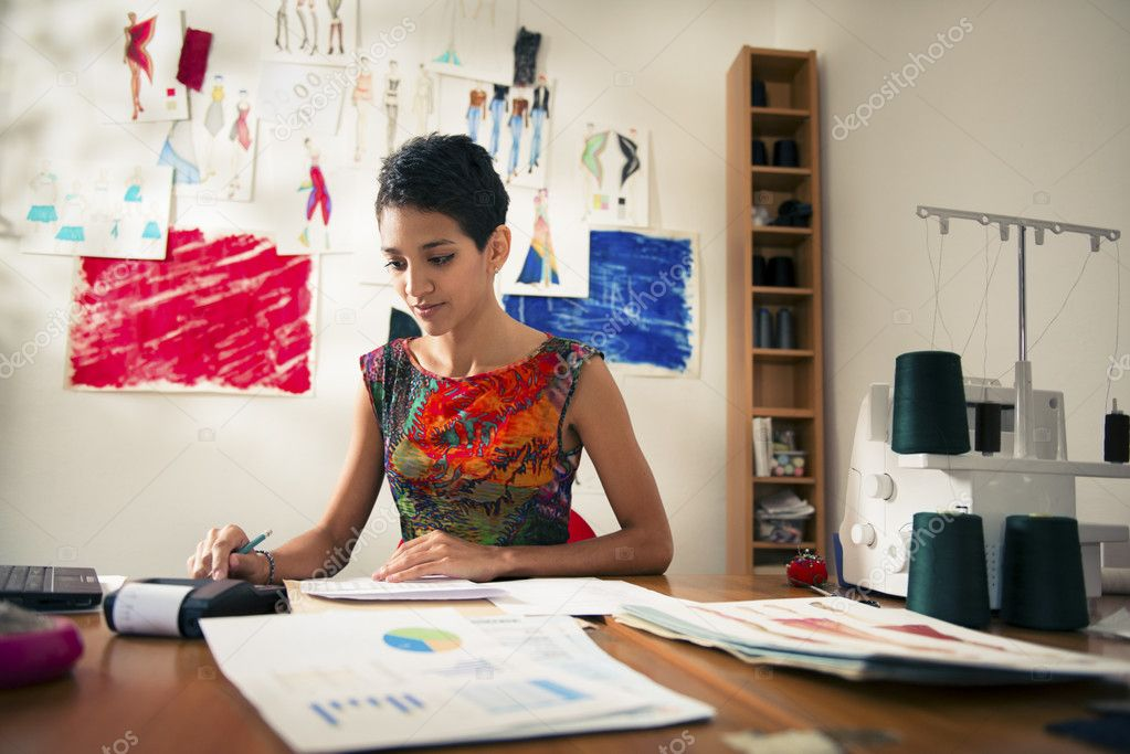 Money and financial planning, young hispanic self-employed woman checking bills and doing budget with calculator, computer and papers in fashion design studio — Stock Photo #13886157