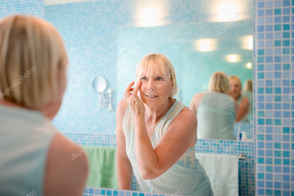Female beauty, senior caucasian woman applying lotion on face in bathroom at home  Stock Photo #13886369