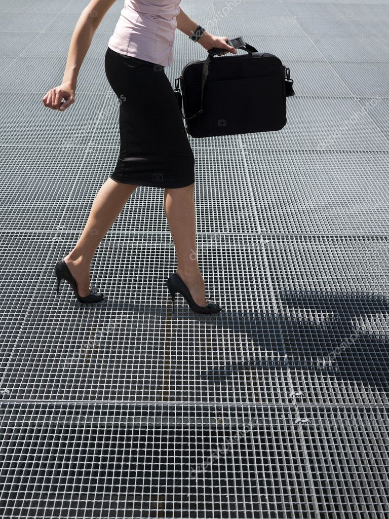 Cropped view of mid adult business woman walking on high heels, trying to balance on grating — Stock Photo #13886922