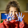 Happy little girl painting with hands in kindergarten - Stok fotoraf