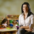 Happy teacher with children eating in kindergarten - Stok fotoğraf