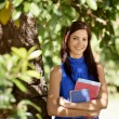 Student portrait at school, happy young woman with university bo — Stock Photo