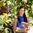 Student portrait at school, happy young woman with university bo — Stock Photo #21233531