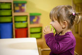 Female child eating green apple in kindergarten — Stock Photo