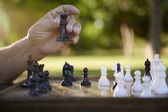 Active retired , senior man playing chess at park — Photo