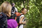 Com mochila fazendo trekking em madeira — Foto Stock