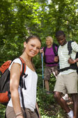 With backpack doing trekking in wood — Stok fotoğraf