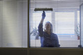 Professional maid cleaning and wiping window in office with soap — Stock Photo