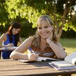 Stock Photo: Young women studying with textbook for college exams at school