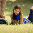 Woman with books and ipad studying for college test — Stock Photo