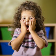 Worried child with mouth open in kindergarten - Stock Photo