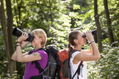 Two women hiking in forest and looking with binoculars — Stock Photo