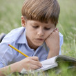 Young school boy doing homework alone, lying on grass — Stock fotografie