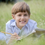 colegial feliz haciendo los deberes y sonriendo, tumbado en la hierba — Foto de Stock