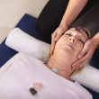 Young therapist arranging crystals on female client for reiki th — Stock Photo