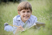 Happy school boy doing homework and smiling, lying on grass — Stock Photo