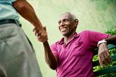 Staré černé a kavkazské muži setkání a třesoucíma se rukama v parku — Stock fotografie