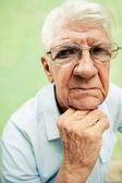 Kameraya el ile çene üzerinde seyir ciddi yaşlı adam portresi — Stok fotoğraf