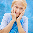 Portrait of surprised senior woman with hands on face on blue ba - Stock Photo