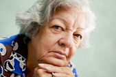 Portrait of serious old woman looking at camera with hands on ch — Stock Photo