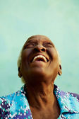 Portrait of funny elderly black woman smiling and laughing — Stock Photo