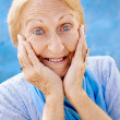 Portrait of surprised senior woman with hands on face on blue ba - Stock fotografie
