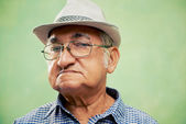 Portrait of serious old man with hat looking at camera — Stock Photo