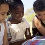 niños y educación, los niños y niñas leyendo el libro en el parque — Foto de Stock