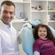 Portrait of child and dentist in dental studio, looking at camer - Stock Photo