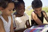 Enfants et l'éducation, enfants et filles lire livre dans le parc — Photo
