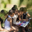 Children and education, kids and girls reading book in park — ストック写真