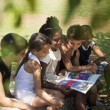 Children and education, kids and girls reading book in park - Stok fotoğraf