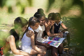 Children and education, kids and girls reading book in park — Stok fotoğraf