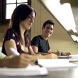Stock Photo: Happy student studying and writing, portrait of hispanic young m