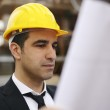 Architect in construction site looking at building plans — Stock Photo