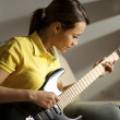 Woman playing and training with electric guitar at home — Stock Photo #27631979