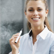 Portrait of young woman smoking electronic cigarette outdoor off — Stock Photo #28613371