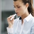 Young woman smoking electronic cigarette outdoor office building — Stock Photo