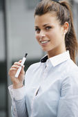 Portrait of young woman smoking electronic cigarette — Stock Photo