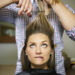 Nervous woman in hairdresser shop cutting long hair — Stock Photo