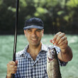Man fishing on river and showing fish to the camera — Stock Photo