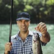 Stock Photo: Mfishing on river and showing fish to camera