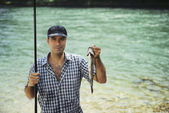 Man fishing on river and showing fish to the camera — Stok fotoğraf