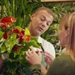 Man in flower shop selling plant to customer — Stock Video #32308407