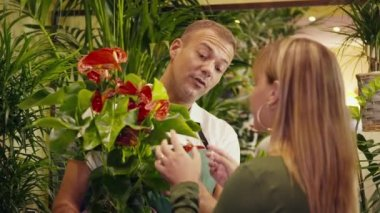 Man in flower shop selling plant to customer — Stock Video