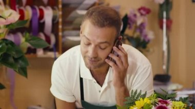 Florist talking with customer on telephone and selling flowers — Stock Video