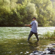 Fisherman standing near river and holding fishing rod — Stock Photo