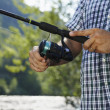 Fisherman standing near river and holding fishing rod — Stock Photo #38005355